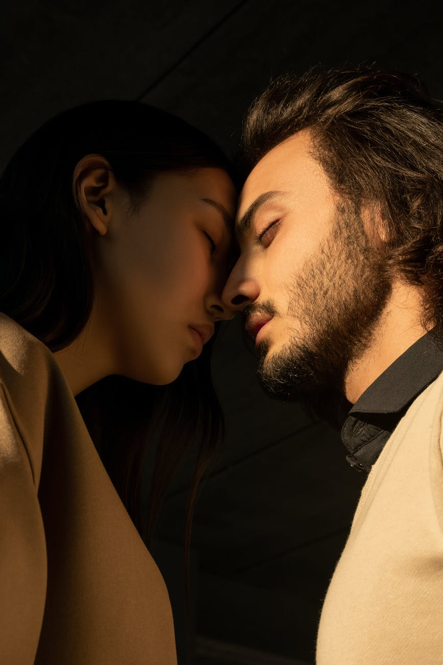 close up photo of couple with their eyes closed facing each other in front of dark background