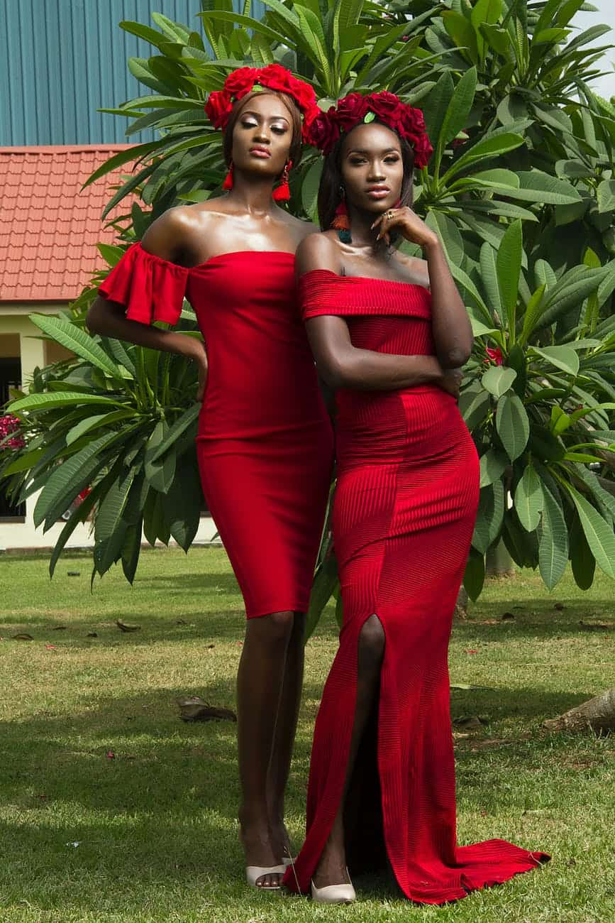 photo of two beautiful women in red dresses and red flower crowns posing in front of green leafed tree