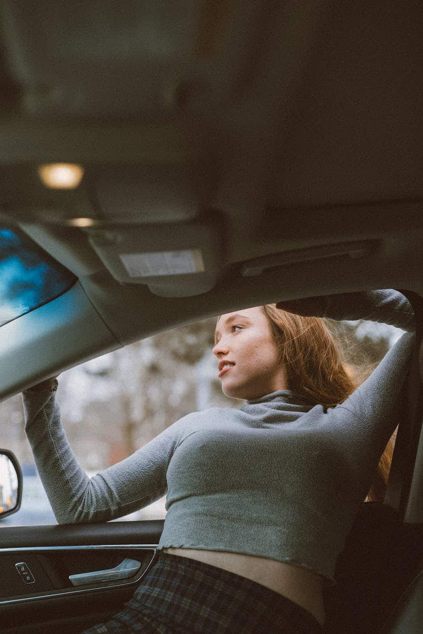 woman getting out of car through window