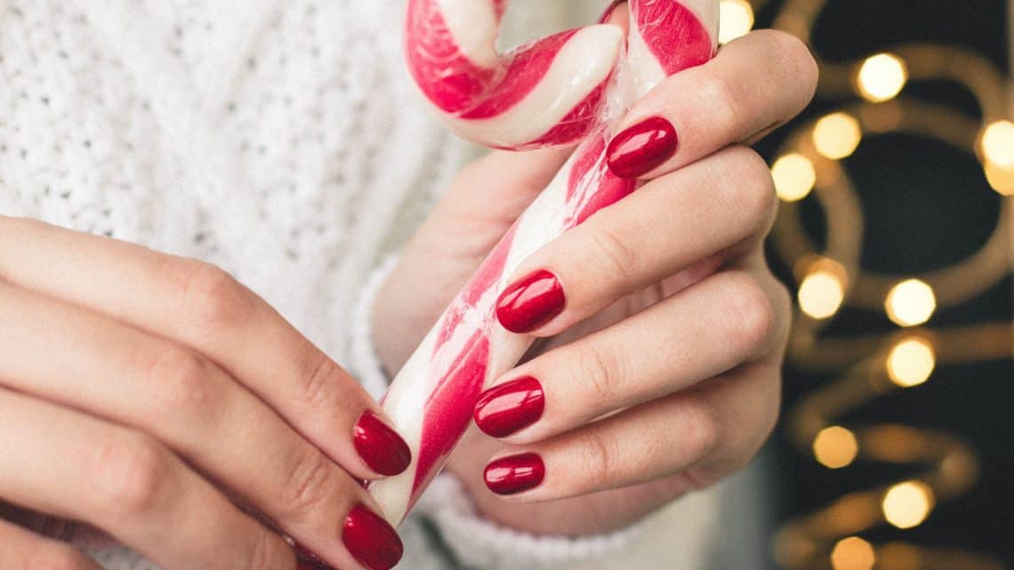 close up photo of person holding candy cane