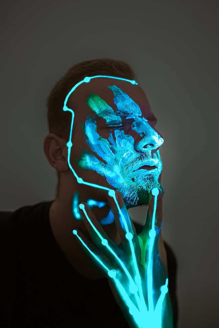 unemotional man with glowing neon body art on face