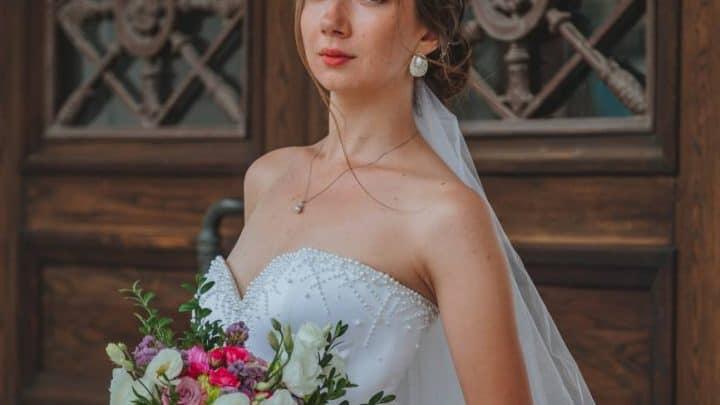 elegant bride standing near wooden door
