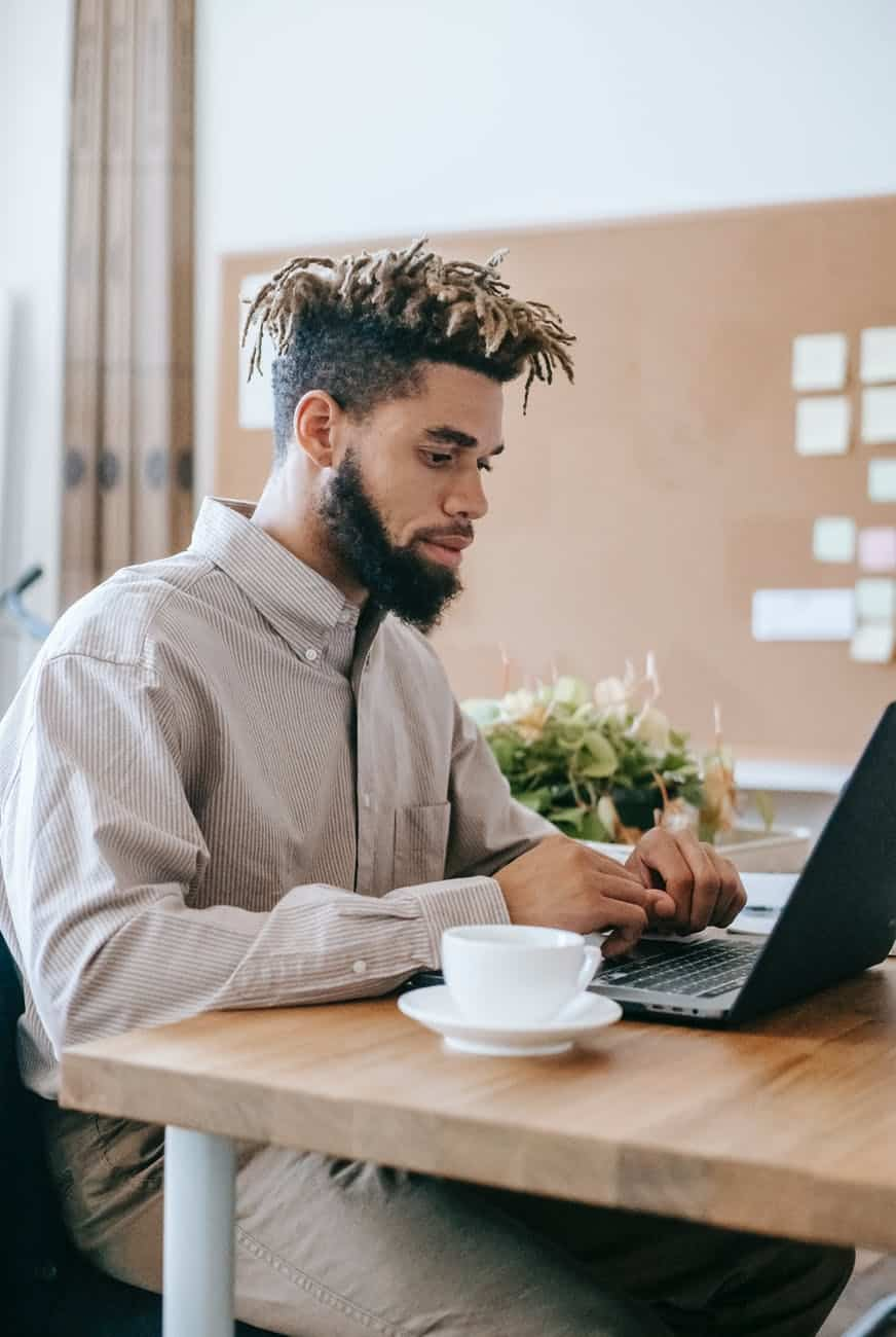man i n dress shirt sitting at the table using laptop computer