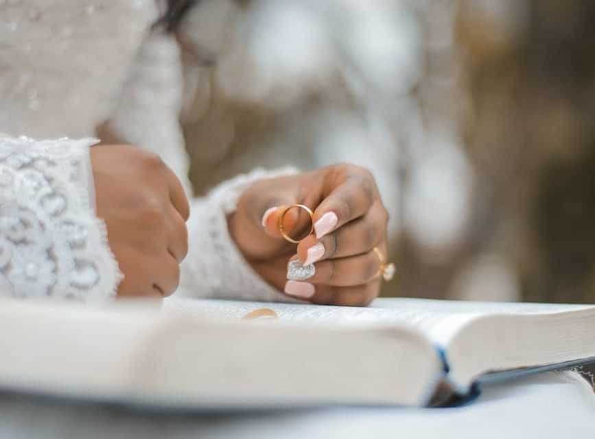 crop bride holding ring and reading wedding vow