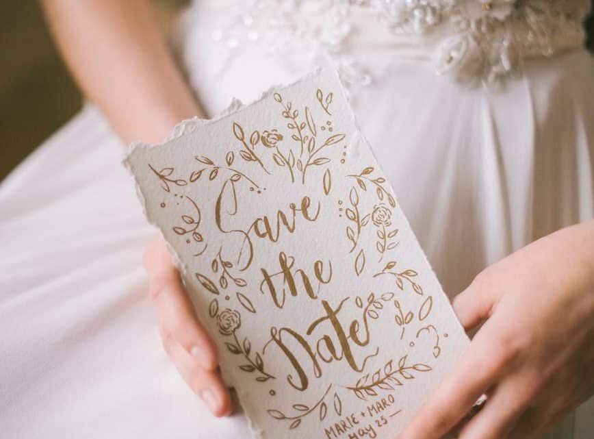 woman in white dress holding a wedding invitation